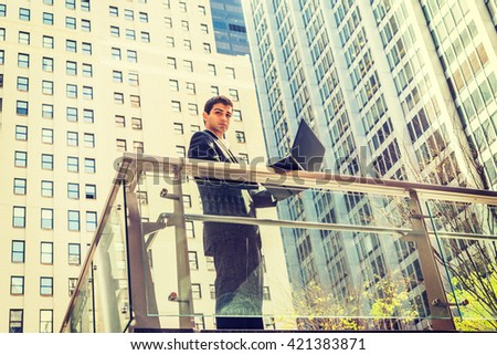 Way to Success. East Indian American student studying in New York, wearing black suit, standing by railing in business district, working on laptop computer, looking away, thinking. Instagram effect  - stock photo