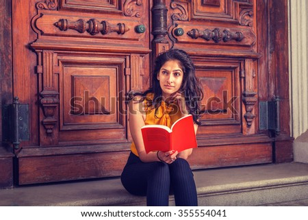 Way to Success. Power of Reading. East Indian American college student studying in New York, sitting on steps in front of vintage style library door way, reading red book, thinking, lost in thought.  - stock photo