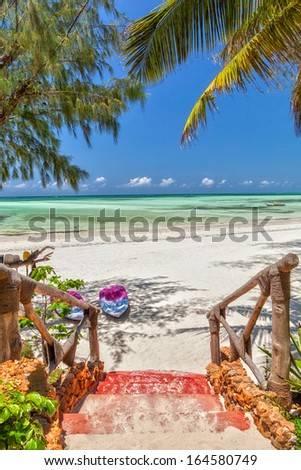 Way to the white sand tropical beach with boats under palm tree leaves at the shore of Indian ocean, Zanzibar, Tanzania