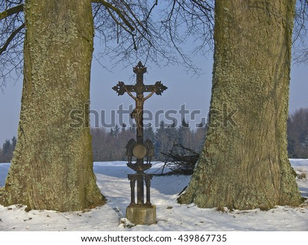 wayside cross between two big trees in winter condition - stock photo