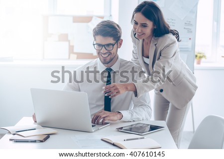 We already have great results! Young beautiful woman pointing at laptop with smile and discussing something with her coworker while standing at office  - stock photo