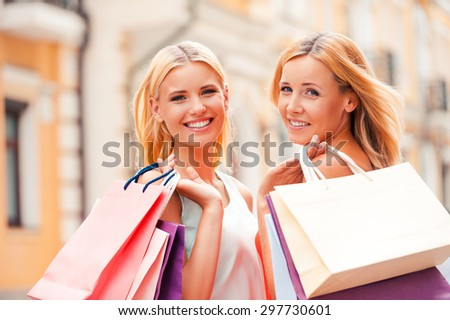 We always go shopping together. Cheerful mature woman and her daughter carrying shopping bags and looking at camera while walking outdoors - stock photo
