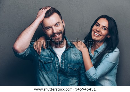 We are better when we together. Studio shot of beautiful young couple in jeans wear standing close to each other and looking at camera with smile - stock photo