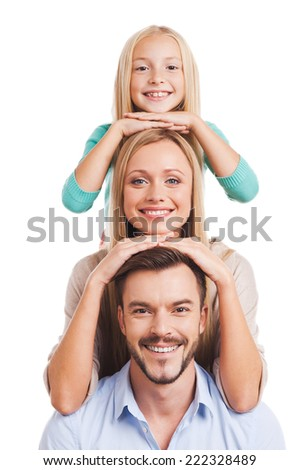 We are family! Happy family of three leaning at each other head and smiling while standing against white background  - stock photo