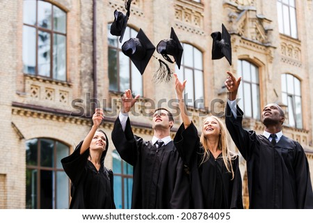 We are finally graduated! Four happy college graduates in graduation gowns throwing their mortar boards and smiling while standing near university - stock photo