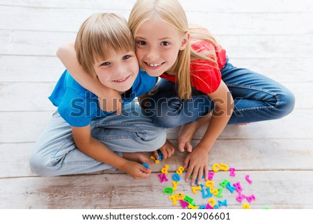 We are good friends! Top view of two cute little children looking at camera and smiling while sitting on the floor and playing with plastic colorful letters  - stock photo