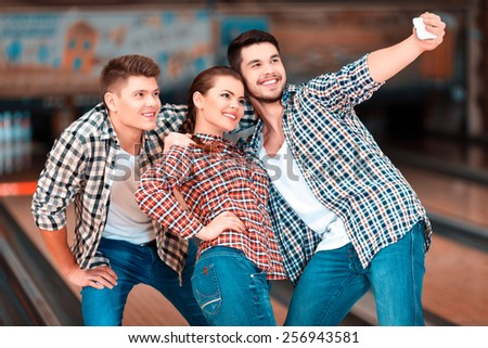 We are happy together. Cheerful friends having fun and doing selfie while spending free time in bowling club - stock photo