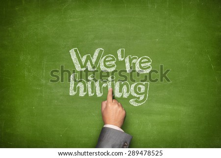 We are hiring concept on green blackboard with businessman hand - stock photo
