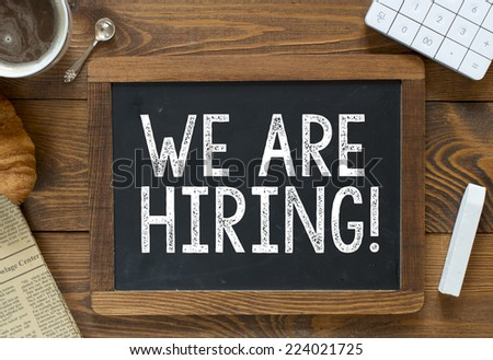 We are Hiring! handwritten with white chalk on a blackboard on a wooden background - stock photo
