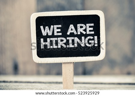 We are hiring handwritten with white chalk on a blackboard on a wooden background