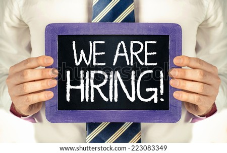 We are hiring ! Man holding blackboard with text We are hiring !  - stock photo