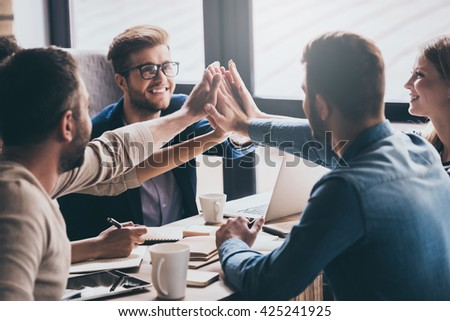 We are leaders on the market! Cheerful young people giving each other high-five with smile while sitting at the office table on business meeting - stock photo