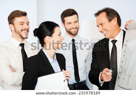 We are making great progress! Confident mature businessman pointing graph on whiteboard and smiling while his colleagues standing near him - stock photo