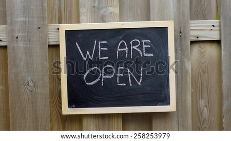 We are open written on a chalkboard hanging outside - stock photo