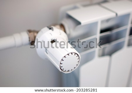 We are saving the central heating - adjuster of warming on the heater - stock photo