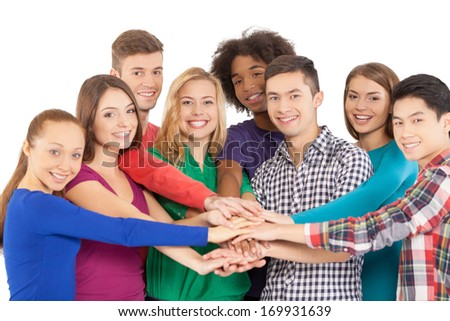 We are strong when we together. Cheerful group of multi-ethnic people holding hands together and smiling at camera while standing isolated on white - stock photo