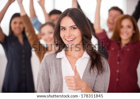 We are successful team! Beautiful young woman showing her thumb up and smiling while group of happy young people standing on background and keeping arms - stock photo