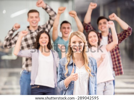 We are successful team! Beautiful young woman showing her thumb up and smiling while group of happy young people standing on background and keeping arms. - stock photo