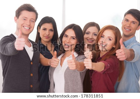We are successful team! Group of cheerful young people standing close to each other and gesturing - stock photo