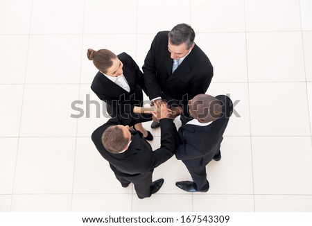 We are team. Top view of four business people in formalwear standing close to each other and holding hands together