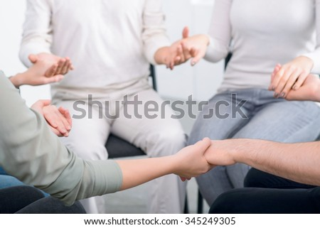 We are the one. Close up of group of people holding hands of each other and sitting in a circle during psychological group  therapy session