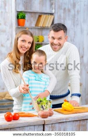 We are the one. Pleasant cheerful smiling family  making salad and feeling content while cooking together - stock photo