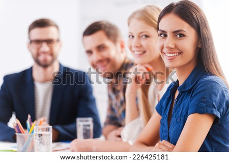 We are the team you can trust. Group of confident business people in smart casual wear sitting at the table together and smiling  - stock photo