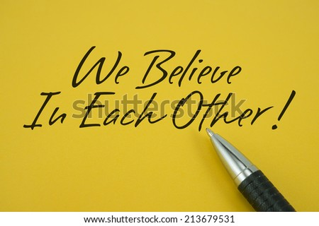 We Believe In Each Other! note with pen on yellow background