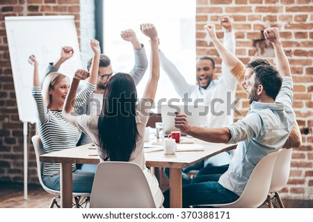 We did it! Group of six cheerful young people keeping arms outstretched and smiling while sitting at the table in office  - stock photo