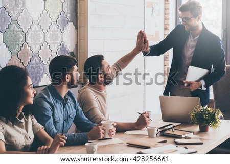 We did it! Two men giving each other high-five with smile while sitting at the business meeting with their coworkers - stock photo