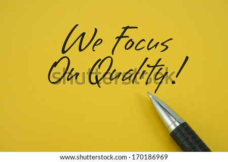 We Focus On Quality! note with pen on yellow background - stock photo