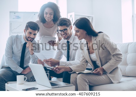 We have great results! Young beautiful woman pointing at her laptop with smile while sitting on the couch at office with her coworkers - stock photo