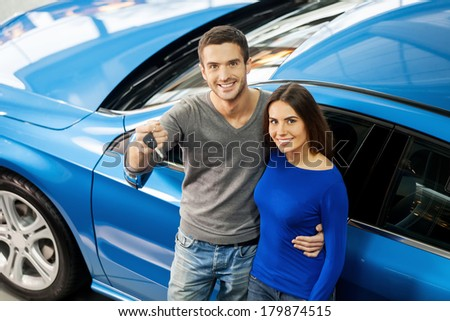 We have made the right choice. Top view of young couple standing near the car at the dealership and holding a key - stock photo