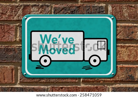 We have Moved Sign,  A teal sign with the word We've Moved with a truck on a brick wall - stock photo