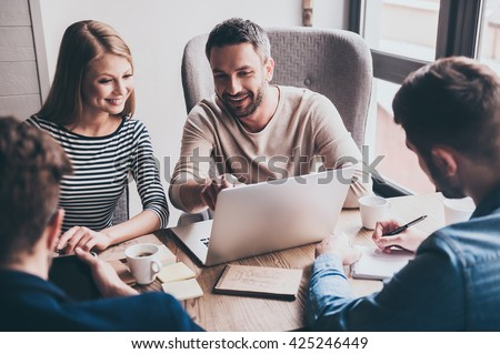 We have positive dynamic! Young handsome man pointing at his laptop with smile while sitting at the office table on business meeting with his coworkers - stock photo