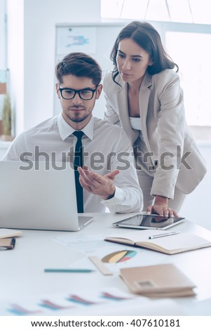 We have some problems with our statistics! Young handsome man in glasses pointing at his laptop and discussing something with his beautiful coworker while sitting at the office table - stock photo