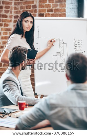We have some space for growth. Beautiful young woman standing near whiteboard and pointing on the chart while her coworkers listening and sitting at the table  - stock photo