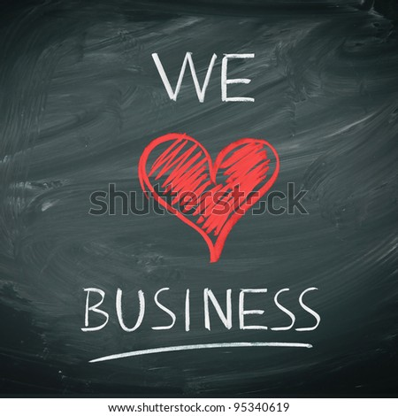 We Love Business. Handwriiten message in chalk on a blackboard incorporating a red heart symbol for love. - stock photo