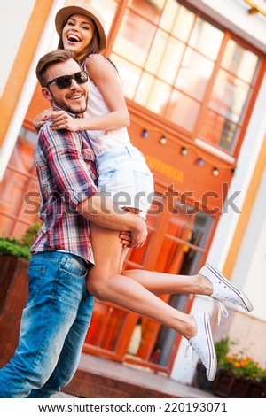 We love each other! Happy young loving couple having fun while standing outdoors - stock photo