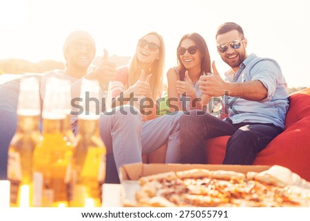 We love pizza and beer! Four young cheerful people showing their thumbs up and smiling while sitting on bean bags with pizza and beer laying on foreground - stock photo