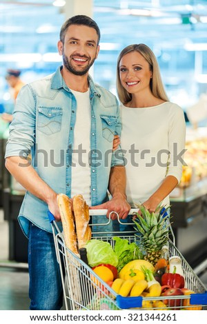 We love shopping together. Happy young couple smiling and looking at camera while standing behind a shopping cart in a food store - stock photo