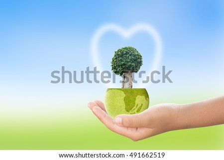 We love the world of ideas,World and tree in human hand on blur nature background