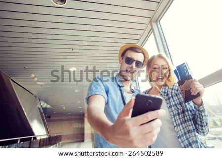 We love traveling! Vacation Selfie. Beautiful young loving couple making selfie by their smart phone while waiting for boarding in the airport. - stock photo