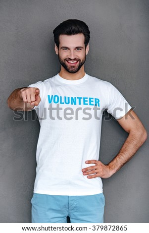 We need you! Confident young man in volunteer t-shirt pointing you and looking at camera with smile while standing against grey background