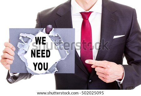 WE NEED YOU message on a ripped paper shown by a businessman
