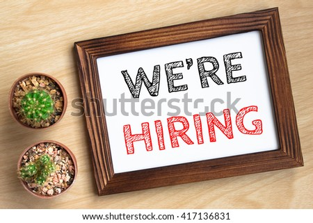 we're hiring, text message on wood frame board on wood table / business concept / Top view - stock photo