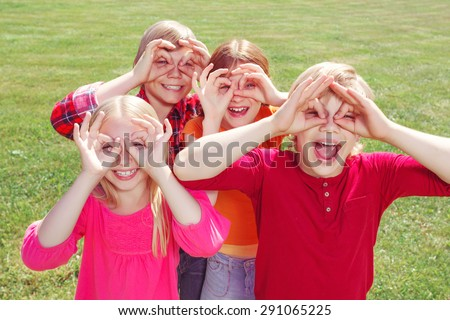 We see you. Nice pleasant children holding their hands on faces imitating binoculars while smiling and having fun in the yard. - stock photo