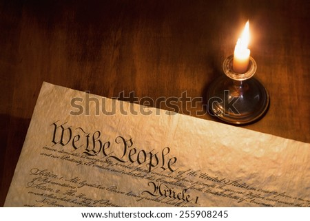 We the People are the opening words of the preamble to the Constitution of the United States illuminated by candle light. - stock photo