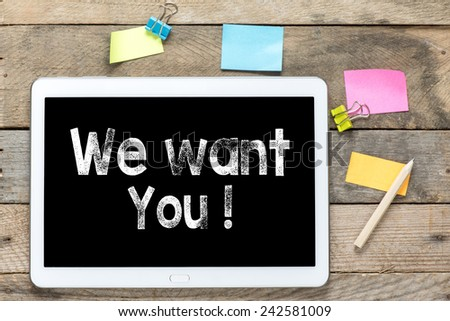 We want you on Tablet computer. Tablet computer with stickers and we want you on the wooden table - stock photo