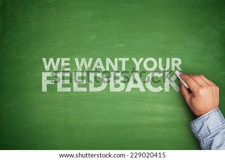 We want your feedback on blackboard with hand - stock photo
